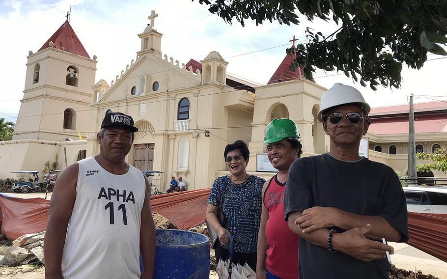 Many residents of Balangiga, Philippines, say they welcome the upcoming return of church bells taken by American troops in 1902. Local government official Sanny Elacion, left, and historian Alicia Valdenor, second from left, pose with construction workers near the rebuilt church, Sept. 20, 2018.