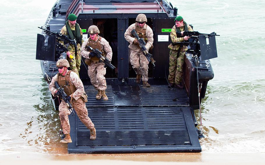 U.S. Marines disembark from a British marine amphibious assault vehicle during a beach landing exercise as part of Trident Juncture 15 in Troia, Portugal, in November 2015.