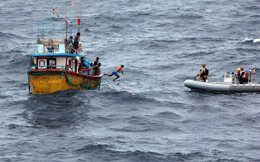 A Sri Lankan fisherman jumps to swim to an inflatable boat from the guided-missile destroyer USS Decatur in the Indian Ocean, Sunday, Oct. 7, 2018.