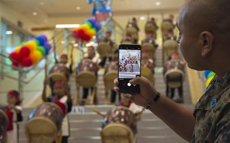 A Marine takes video of a taiko drumming performance by Zukeran Elementary students during a ribbon-cutting ceremony for the new school at Camp Foster, Okinawa, Wednesday, Oct. 10, 2018.