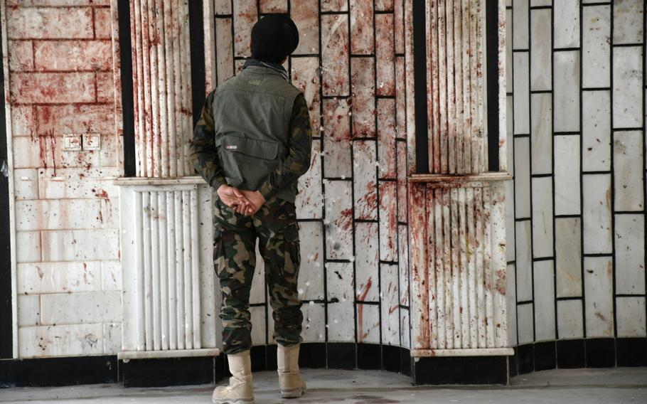 An Afghan security official looks at blood on the walls of the Imam Zaman mosque in Kabul, Afghanistan, on Oct. 21, 2017, a day after an Islamic State suicide bomber launched a deadly attack on the mosque.