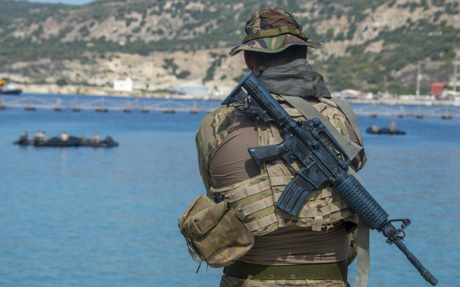 A Greek navy special forces sniper watches maritime operations during training with U.S. forces in Souda Bay, Greece, on Sept. 11, 2018.