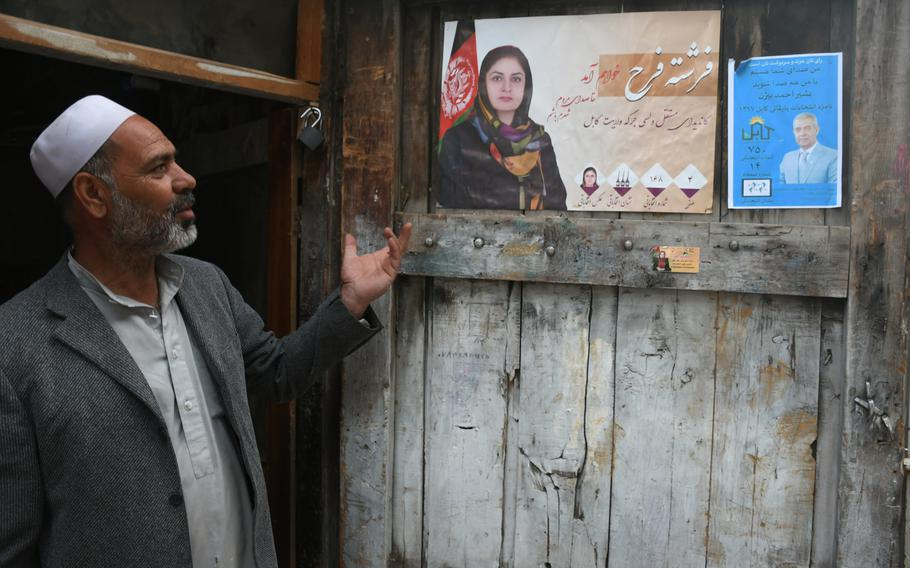 Ghulam Qadir, 60, speaks of the parliamentary candidates he supports, whose election posters adorn his carpentry shop in Kabul, on Wednesday, Oct. 10, 2018.