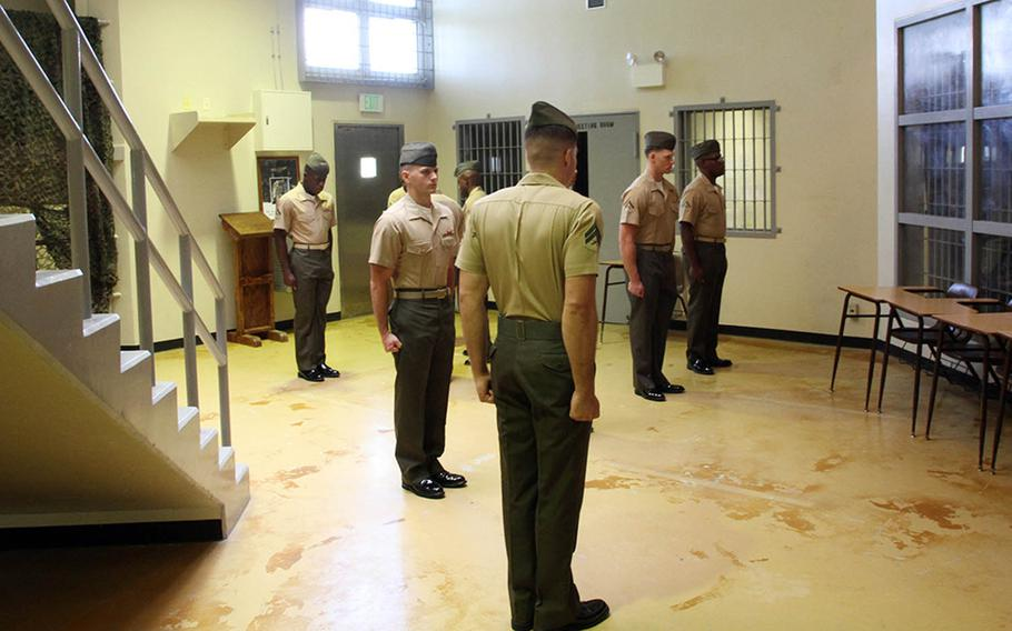 Marines from a Correctional Custody Unit class stand at attention for a uniform inspection at the brig on Camp Hansen, Okinawa, Aug. 31, 2018.