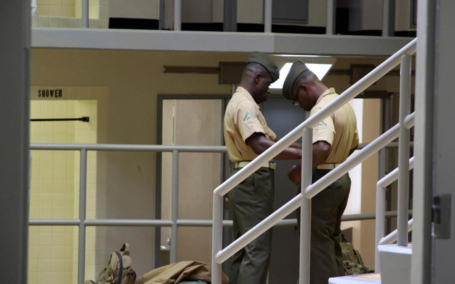 A Marine helps another prepare for a uniform inspection during the Correctional Custody Unit program in August at Camp Hansen, Okinawa.