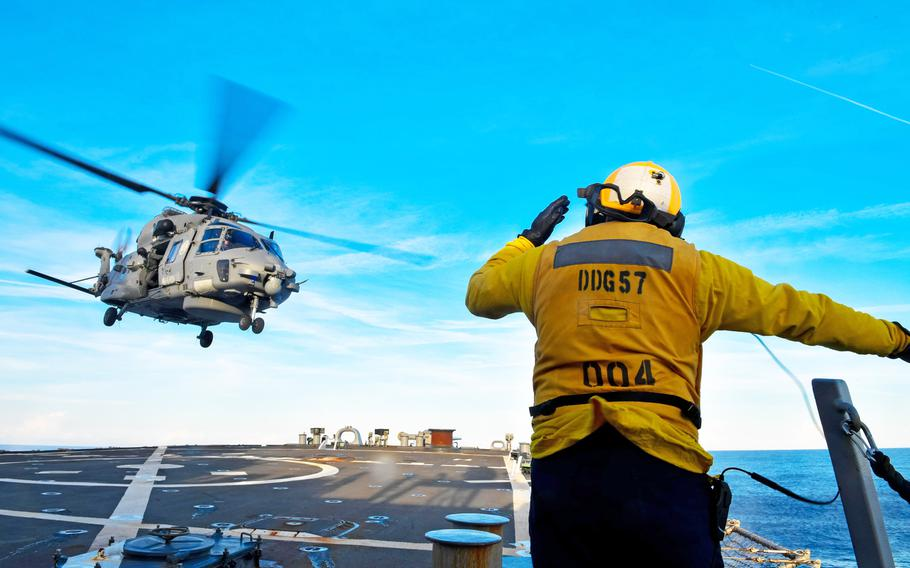 An SH-90 helicopter from the Italian frigate Virgino Fasan hovers above the destroyer USS Mitscher on Oct. 7, 2018, in the Mediterranean Sea during exercise Mare Aperto.