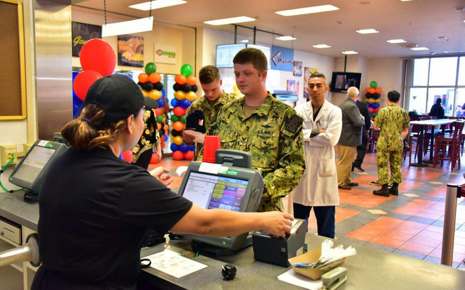 A sailor orders a meal at a new 24-hour food court near the waterfront at Yokosuka Naval Base, Japan, Monday, Oct. 22, 2018.