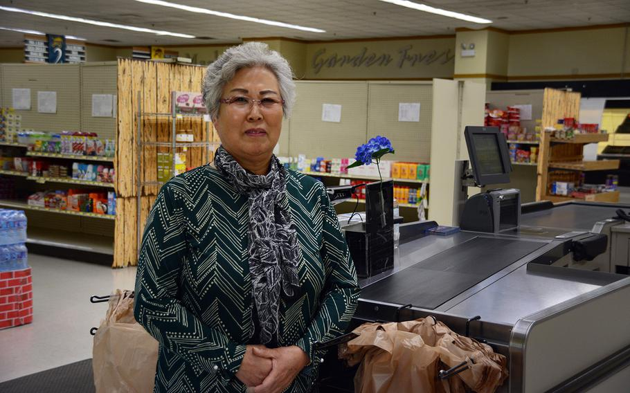 Lee Jong-Sook, 69, who has worked as a bagger at the Camp Red Cloud commissary since 2001, poses at her station, Sunday, Oct. 21, 2018.