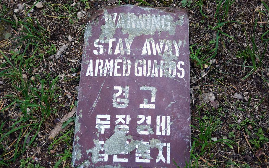 An old sign lays on the grass along the Green Mile, a running trail consisting of steep stairs along the edge of Camp Red Cloud, South Korea, Sunday, Oct. 21, 2018.