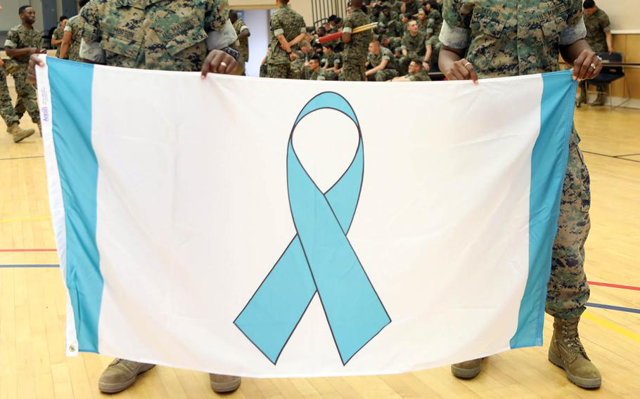 Marines hold up a banner featuring a Sexual Assault Prevention and Response ribbon at Camp Johnson, N.C., April 27, 2018.
