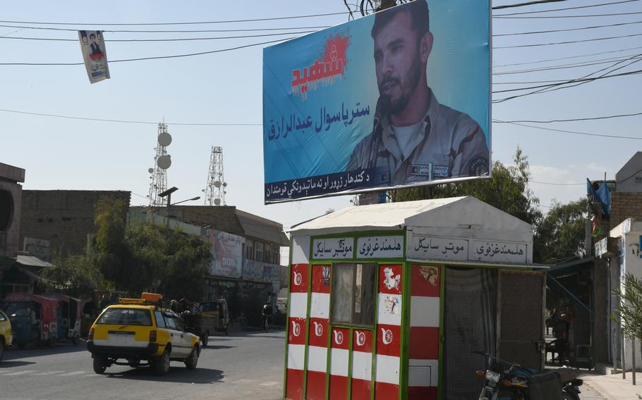 A billboard depicting former Kandahar police chief Gen. Abdul Raziq towers over a busy intersection in Kandahar City on Thursday, Oct. 25, 2018, one week after Raziq was assassinated in an attack that also injured a top U.S. general.