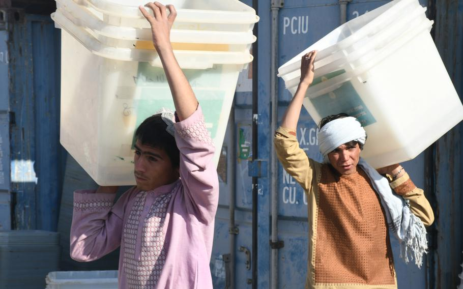 Boys at an election office in Kandahar help load trucks with ballot boxes on Friday, Oct. 26, 2018. The boxes will be dispersed at local polling centers ahead of voting on Oct. 27.