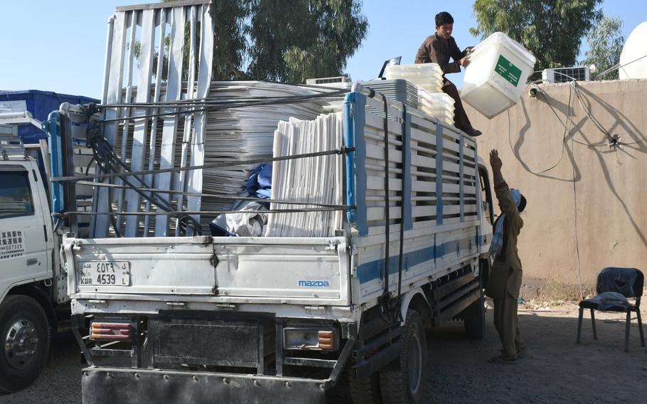 Boys at an election commission office in Kandahar help load trucks with ballot boxes on Friday, Oct. 26, 2018. The boxes will be dispersed at local polling centers ahead of voting on Oct. 27.