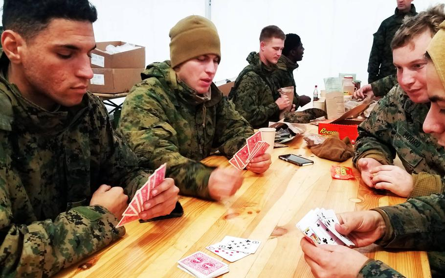 Marines playing cards with their warming layers on during chow at Exercise Trident Juncture, near Rennebu, Norway, Wednesday, Oct. 31, 2018.