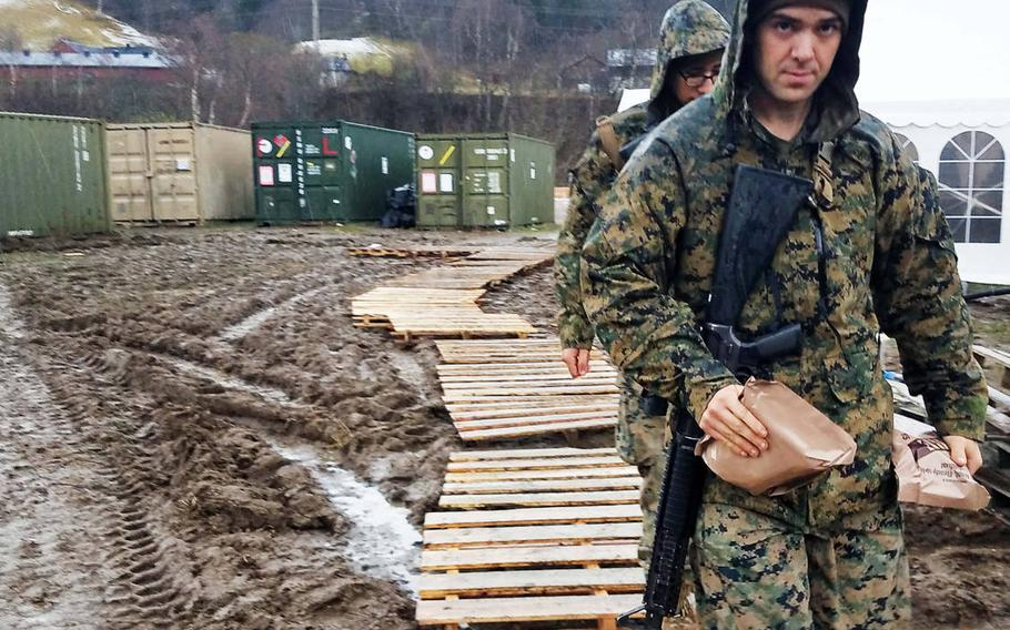 Marines bring MREs into a tent, to get out of the rain and cold, at Exercise Trident Juncture, near Rennebu, Norway, Wednesday, Oct. 31, 2018.