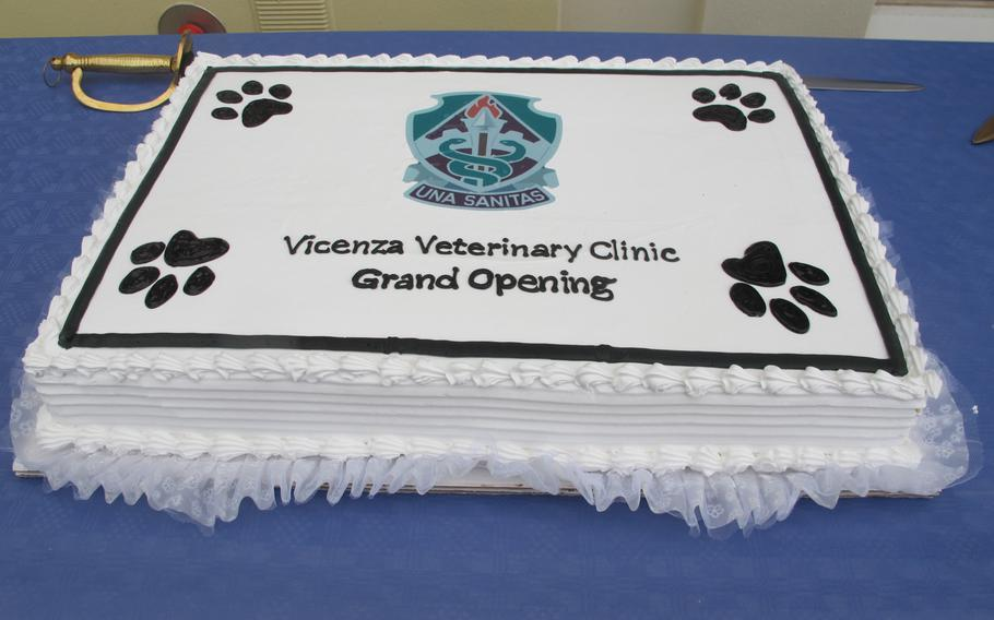 """A cake and sword are displayed at the opening of Vicenza's new veterinary treatment facility, located at the back of the garrison health center. Dog treats were also on hand, although a sign was confusingly posted reading """"No pets allowed."""""""