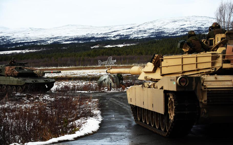 Marines in an M1A1 tank drive past an enemy Leopard 2E tank declared a casualty, played by the Spanish Army, during the simulated Battle of Oppdal, part of Exercise Trident Juncture, in Oppdal, Norway, Thursday, Nov. 1, 2018.