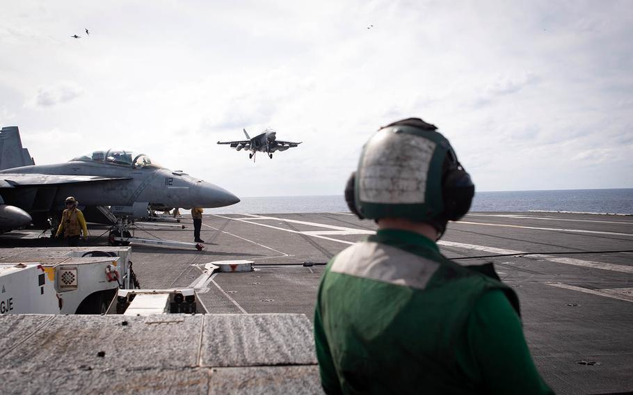 A hook-runner awaits the landing of an F-18 Super Hornet aboard the USS Ronald Reagan during Keen Sword drills at sea, Saturday, Nov. 3, 2018.