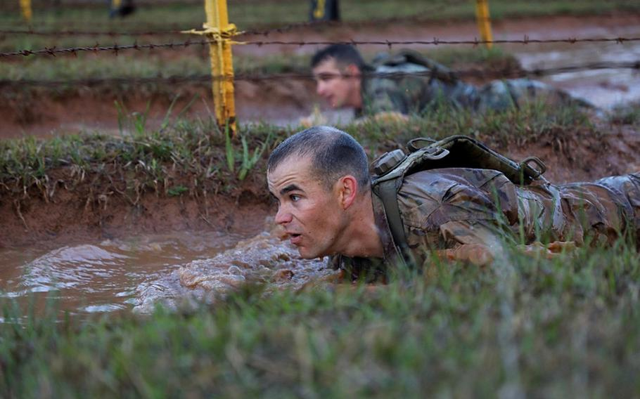 A U.S. Army Ranger low crawls under barbed wire at Malvelsti during the 35th annual David E. Grange Jr. Best Ranger Competition on Fort Benning Ga., April 13, 2018. The three-day event tests competitors' physical, mental, and technical capabilities.