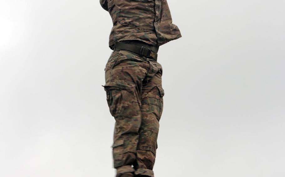 Staff Sgt. Carlos Mercado, a Delta Company, 1st Battalion, 505th Parachute Infantry Regiment, 3rd Brigade Combat Team paratrooper, prepares to drop into Victory Pond after slapping the coveted Ranger Tab during the combat water survival assessment portion of the Best Ranger Competition at Fort Benning, Ga., on Apr. 15, 2018. After dropping into the pond, competitors swim to shore, pick up a zip line pulley, run to and finally ascend a 75-foot-high tower.