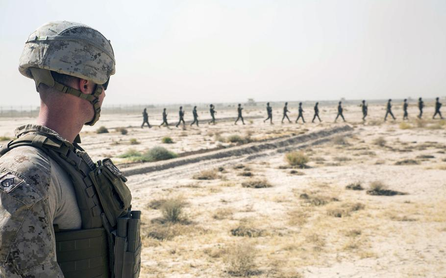 A U.S. Marine with Task Force Southwest observes Afghan soldiers move to the rally point to begin their training during a live-fire range at Camp Shorabak in June 2018.