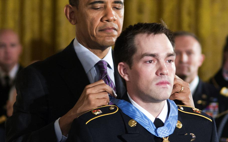 President Barack Obama presents the Medal of Honor to former Army Staff Sgt. Clinton Romesha during a ceremony at the White House, Feb. 11, 2013.