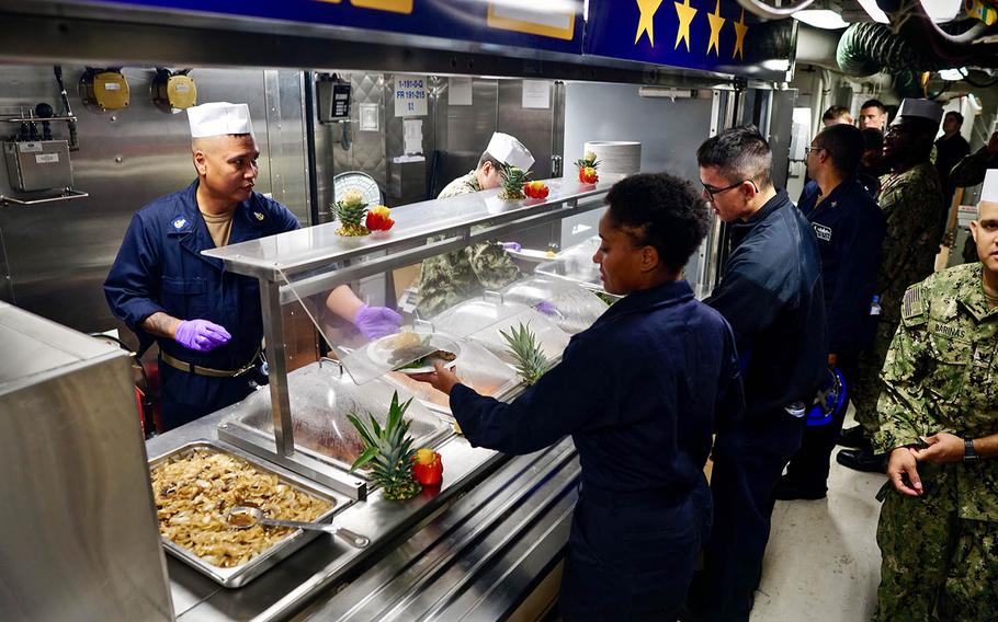 Sailors aboard the USS John S. McCain serve and receive food at the newly opened Maverick Cafe, Monday, Nov. 19, 2018. The collision-damaged ship is undergoing repairs at Yokosuka Naval Base, Japan.