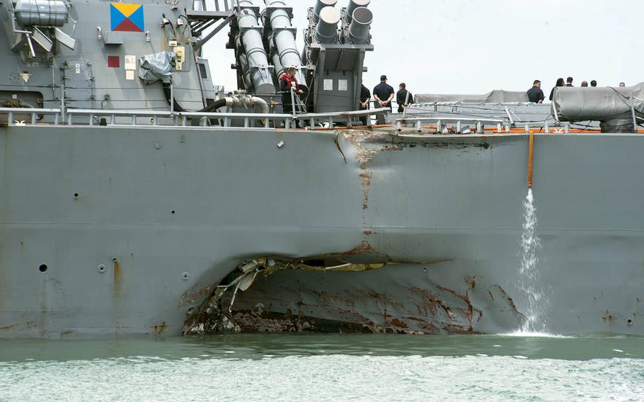 Portside damage is visible as the USS John S. McCain steers towards Changi Naval Base, Singapore, after a collision with a merchant vessel, Aug. 21, 2017. Ten sailors were killed in the incident.