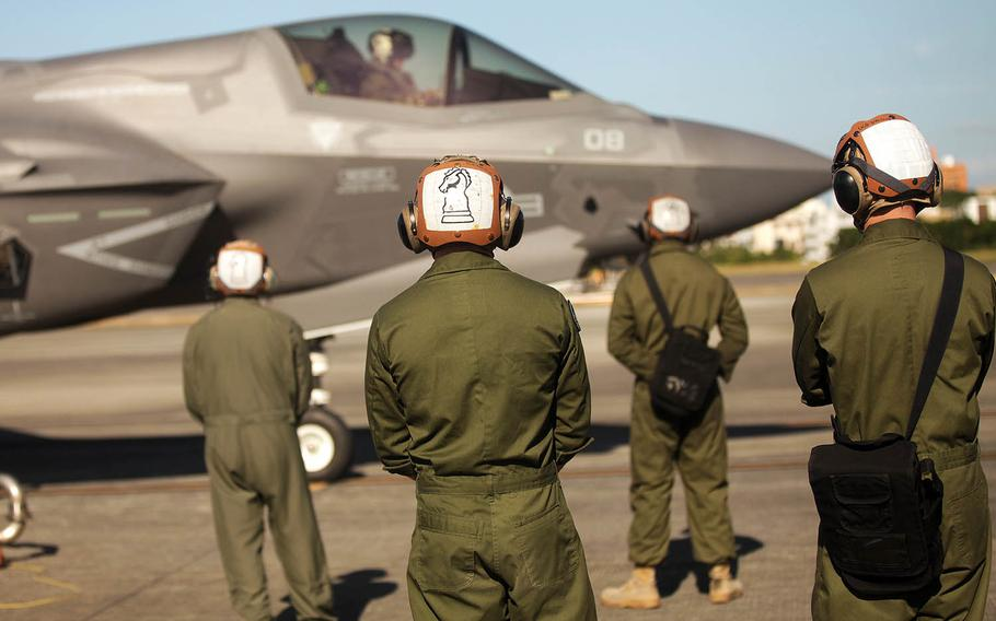 Marines stand by while an F-35B Lightning II jet refuels at Marine Corps Air Station Futenma, Okinawa, Tuesday, Nov. 27, 2018.