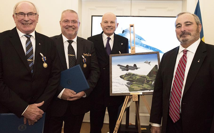 From left to right, Col. Lars-Erik Blad, Maj. Roger Moeller, Maj. Krister Sjober, and Retired U.S. Air Force Lt. Col. Tom Veltri stand beside the official photo which depicts the event that earned the Swedish pilots their U.S. Air Medals in Stockholm, Sweden, Nov. 28, 2018. The Swedish pilots risked their lives to save an SR-71 and its aircrew, Tom Veltri and Duane Noll, on June 29, 1987.