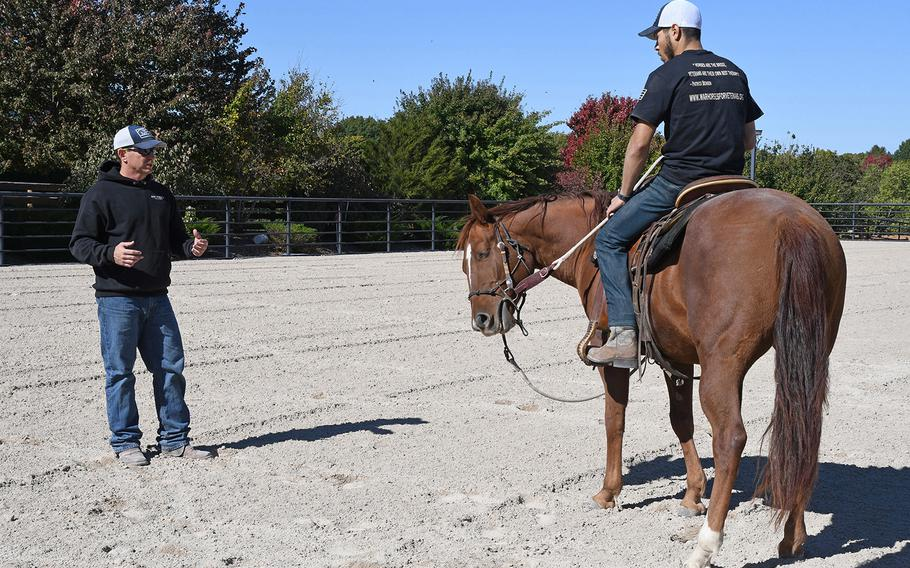 Patrick Benson, co-founder and director of War Horses for Veterans, explains the importance of relaxing and breathing when you ride, to a combat veteran during the nonprofit's October program.