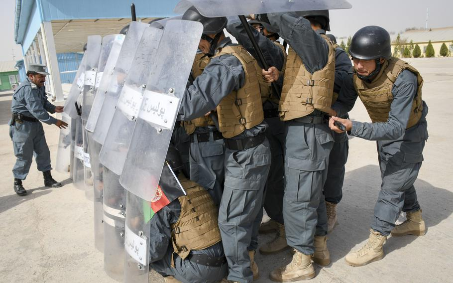 Afghan police in training form a defensive phalanx amid a hail of rocks as an instructor inspects them during a crowd-control drill at the Regional Police Training Center in Herat, Oct. 28, 2018. Responsibility for training police primarily belongs to Afghan mentors, with allied troops now focusing on advising at higher echelons and with Afghan special operations.    J.P. Lawrence/Stars and Stripes