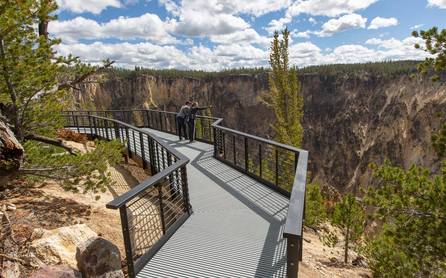 Visitors look out off Inspiration Point in the Grand Canyon of  Yellowstone National Park. Servicemembers and their immediate family members are eligible for a free annual national park pass, though most are currently closed due to the federal budget impasse.
