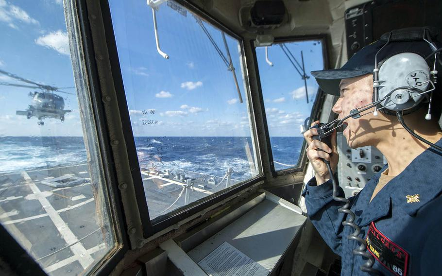 Ensign Thanh Xuong Giang relays information to the air and deck crew aboard the guided-missile destroyer USS McCampbell in the East China Sea, Dec. 27, 2018.