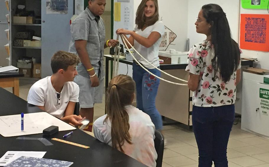 Geometry students use a rope to show how to calculate a triangle during class at Naples High School near Naples, Italy. The Department of Defense Education Activity plans to increase class sizes in its middle and high schools next year, a decision that would reduce staff by about 300.