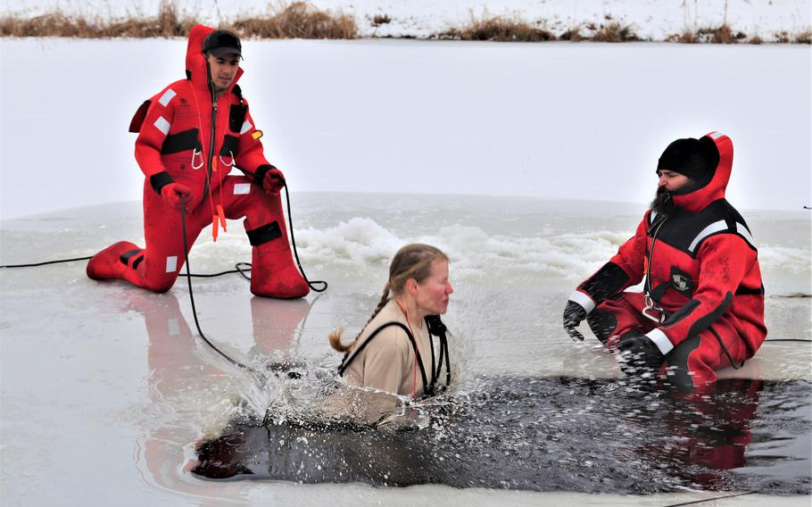 A soldier takes the plunge into a hole cut into ice-covered Big Sandy Lake as part of cold-water immersion training of the Cold-Weather Operations Course on Dec. 13, 2018, at Fort McCoy, Wis.
