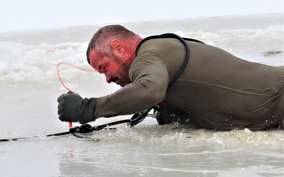 A soldier climbs out of a hole cut into ice-covered Big Sandy Lake after jumping in the water as part of cold-water immersion training of the Cold-Weather Operations Course on Dec. 13, 2018, at Fort McCoy, Wis.