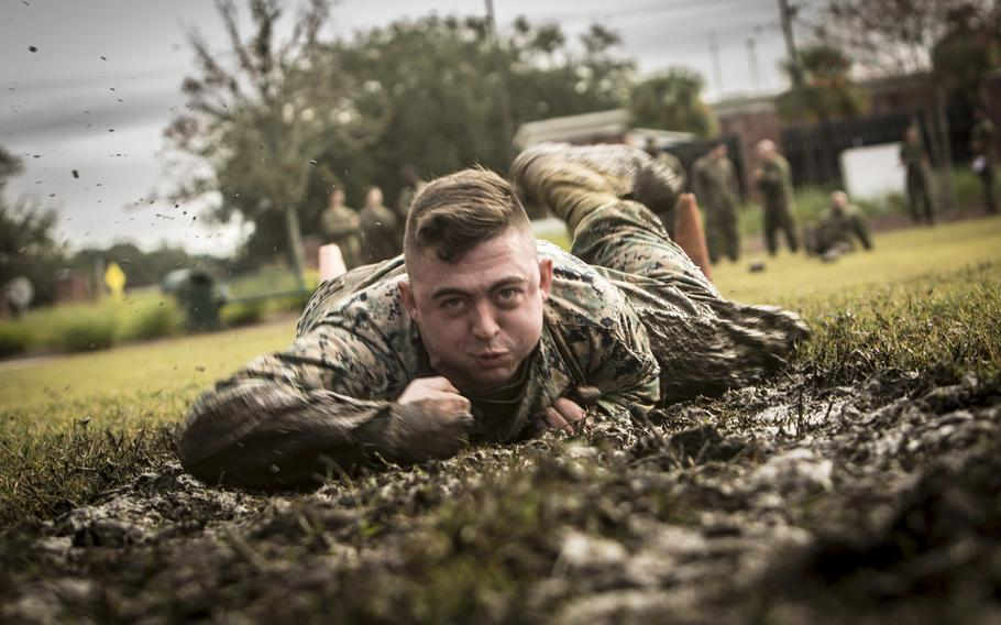 Cpl. Darrell Reynolds, 4th Marine Logistics Group, Marine Forces Reserve, low crawls during the maneuver under fire portion of the combat fitness test at Marine Corps Support Facility New Orleans, Dec. 14, 2018.