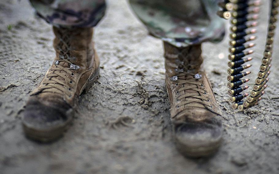 The Army is testing new combat boots in a push to better compete with the more comfortable commercial brands favored by many soldiers for their lightness. Here, a soldier from the 1-114th Infantry Regiment stands in the mud holding 7.62mm ammunition during training on Joint Base McGuire-Dix-Lakehurst, N.J., Nov. 6, 2018.