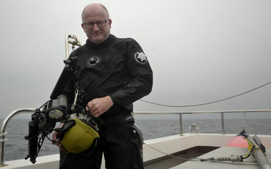 Deeper Dorset diver, photographer and photogrammetry expert Simon Brown poses with his underwater camera after diving to survey a Republic P-47D Thunderbolt crash site in Weymouth Bay, England,  May 24, 2018.''What you're looking for is really discrete things in the seabed,'' Brown said.