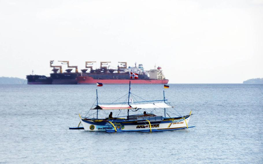 A tourist boat drifts in front of a massive commercial vessel near Baloy Beach in Subic Bay, Philippines, in March 2015.