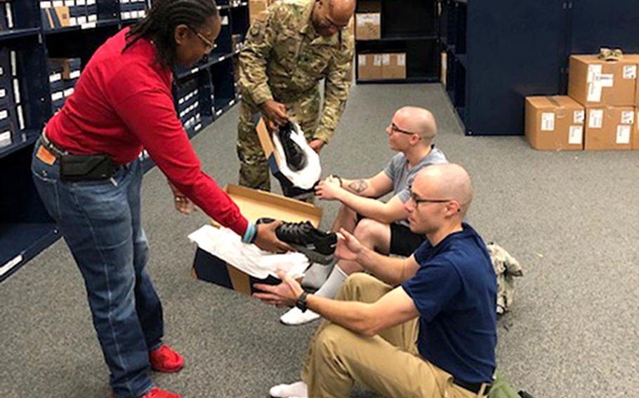 Air Force recruits Daniel Sterling, right, and Ryan Padro, second right, try on shoes at Joint Base San Antonio-Lackland, Texas, Jan. 3, 2019.