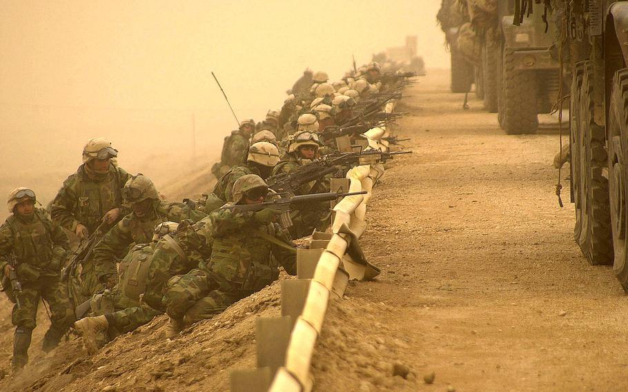 U.S. troops line up behind a road barrier as they secure a key bridge along a main supply route during the march to Baghdad, Iraq, March 2003.