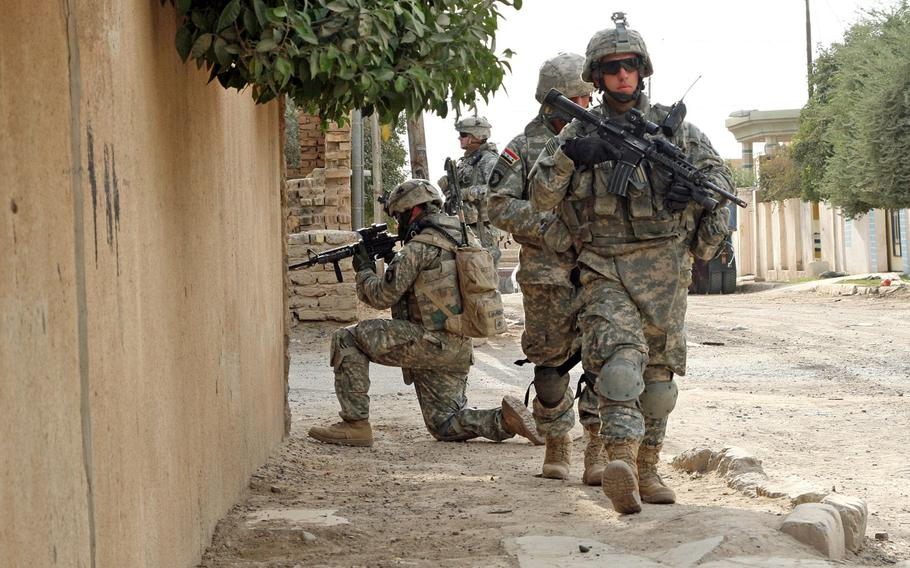 First Lt. Erich Almonte, 27, of Miami, an Iraqi interpreter and other soldiers of 2nd Battalion, 327th Infantry Regiment, 101st Airborne Division move cautiously down a street during a patrol Friday in Samarra, Iraq in 2007.