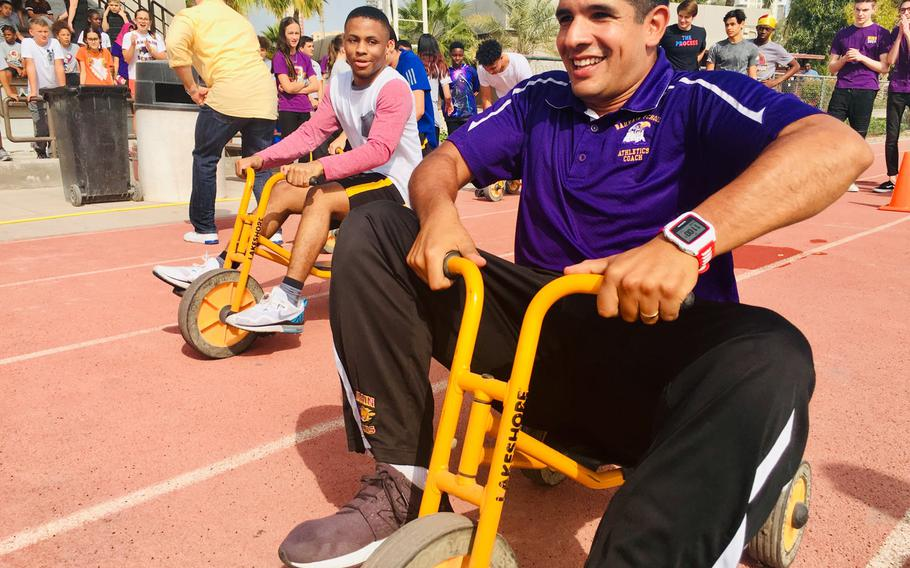 Emiliano Herrera, a teacher and basketball coach, participates in a trike race during homecoming events at Bahrain School on Jan. 17, 2019. The school is celebrating 50 years this week with events, alumni and basketball games.