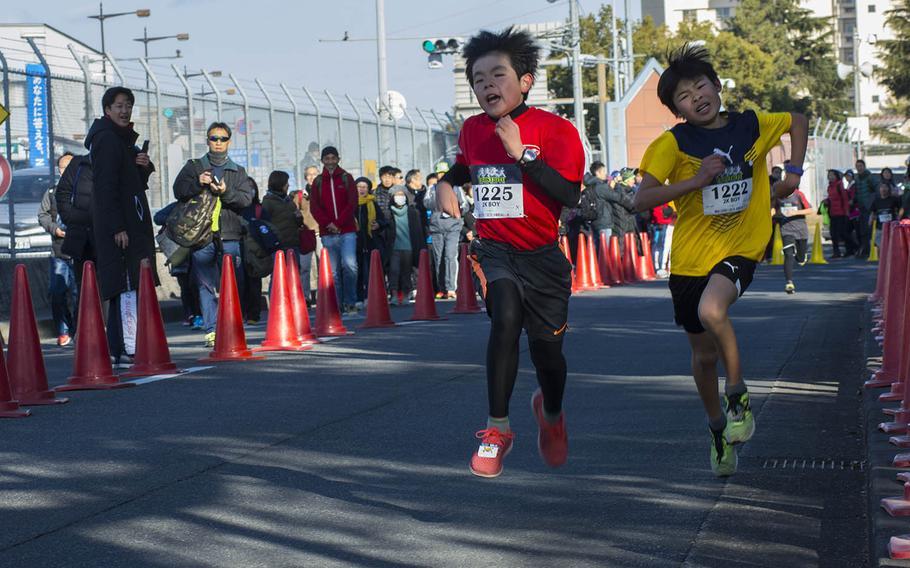 A couple of kids run hard during the 38th annual Yokota Striders Frostbite Road Race at Yokota Air Base, Japan, Sunday, Jan. 20, 2019.