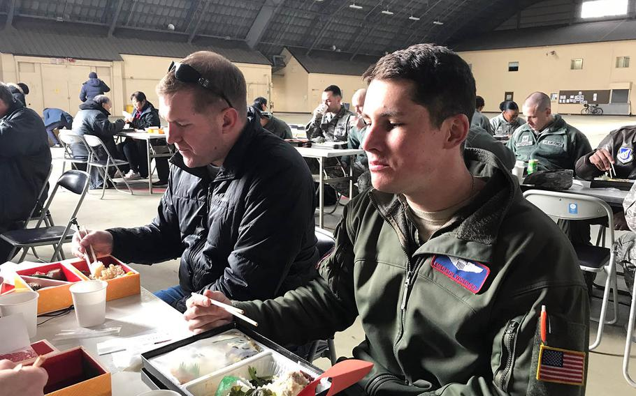 """Air Force captains Jonathan Coffey, left, and Emerson Woerner eat lunch with others involved in the filming of """"Fukushima 50"""" at Yokota Air Base, Japan, Monday, Jan. 28, 2019."""