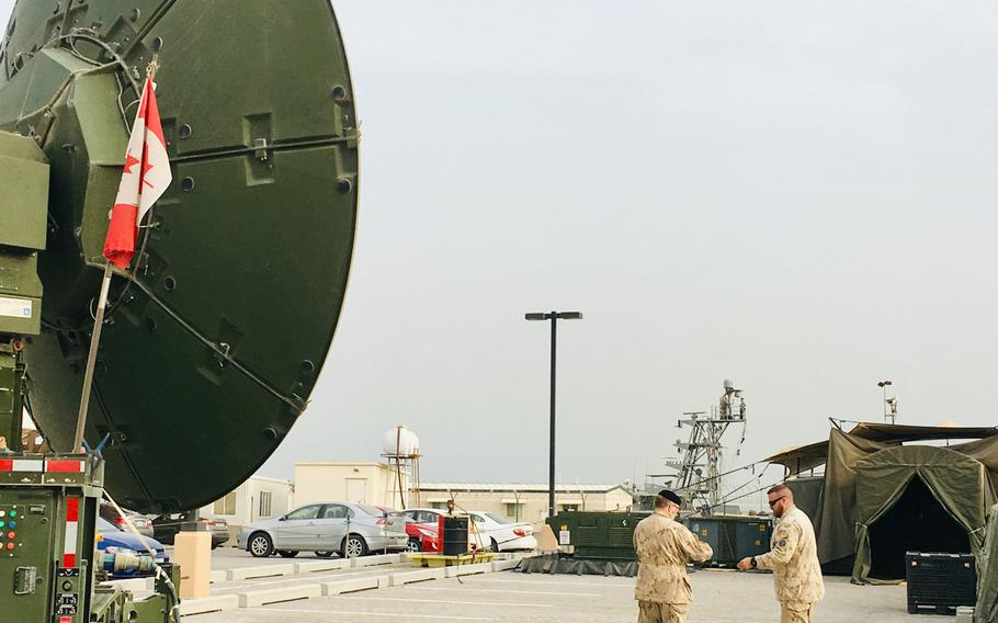 Canadian military members from Combined Task Force 150 stand next to a satellite dish on Naval Support Activity Bahrain, Jan. 23, 2019. The team made up of 30 Canadians and seven Australians work with 10 other Canadians running the Unclassified Remote-Sensing Situational Awareness satellite system. URSA monitors maritime traffic in the Persian Gulf and the historic narcotics ''smack track'' in the Arabian Sea and Indian Ocean.