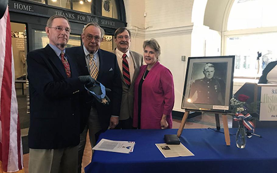 Courtney nephews unveil a replica of their Marine uncle's Medal of Honor on Nov. 12 at the St. Louis County Historical Society's Veterans' Memorial Hall in Duluth, Minn. From left, Courtney Storey, Ben Storey, Bob Storey and his wife, Lynn Storey.