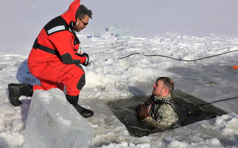 Instructor Bill Hamilton keeps an eye on a soldier during cold-water immersion training as part of the Cold-Weather Operations Course, Jan. 17, 2018, at Fort McCoy, Wis.